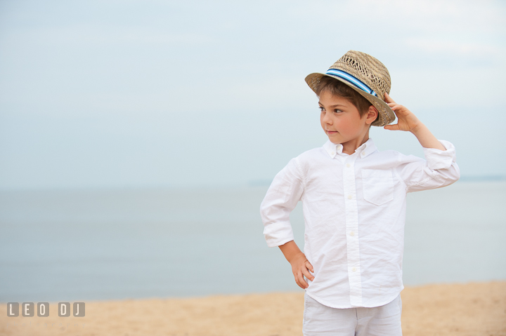 Young boy smiling and posing with his straw fedora hat. Chesapeake Bay, Kent Island, Annapolis, Eastern Shore Maryland children and family lifestyle portrait photo session by photographers of Leo Dj Photography. http://leodjphoto.com