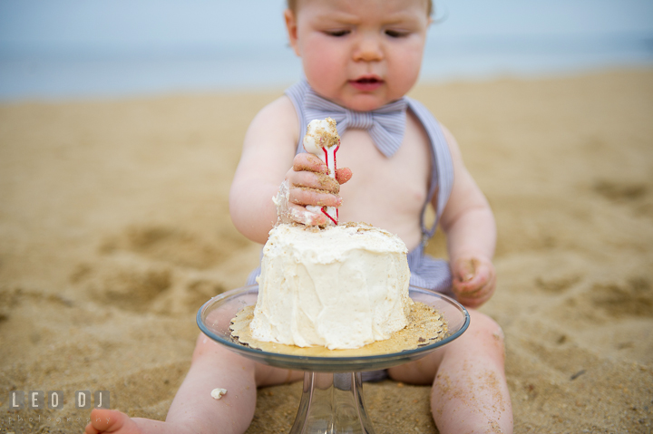 Little baby boy on beach trying to put the year one candle on birthday cake
