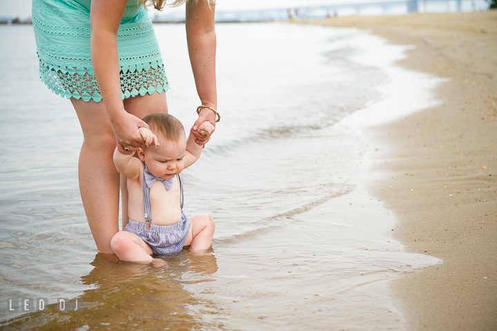Mother holding child tasting the little water waves on the beach. Chesapeake Bay, Kent Island, Annapolis, Eastern Shore Maryland children and family lifestyle portrait photo session by photographers of Leo Dj Photography. http://leodjphoto.com