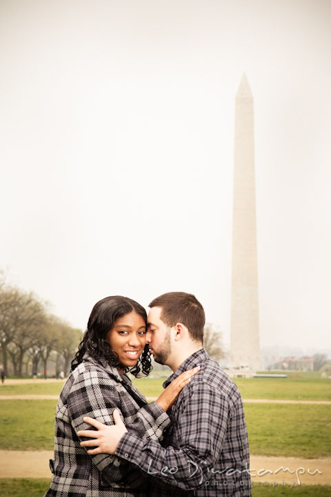 Engaged guy cuddled his fiancée with the National Monument in the background. Pre wedding engagement photo session the Mall, National Monument, The Capitol, Washington DC by wedding photographer Leo Dj Photography