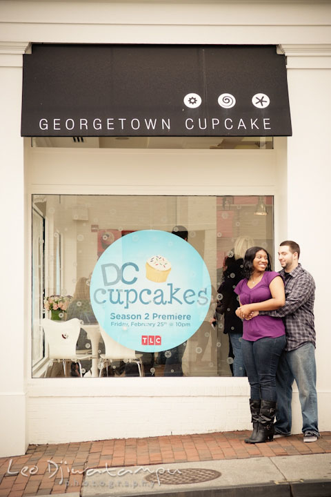 Engaged guy and girl cuddling by the Georgetown Cupcake shop, DC cupcake TLC sign. Pre wedding engagement photo session at Georgetown, Washington DC by wedding photographer Leo Dj Photography
