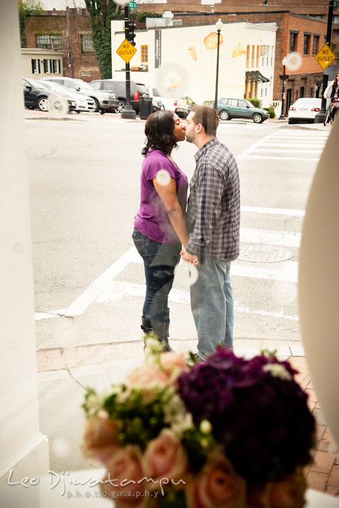 Engaged guy and his fiancée kissing outside on the street. Pre wedding engagement photo session at Georgetown, Washington DC by wedding photographer Leo Dj Photography