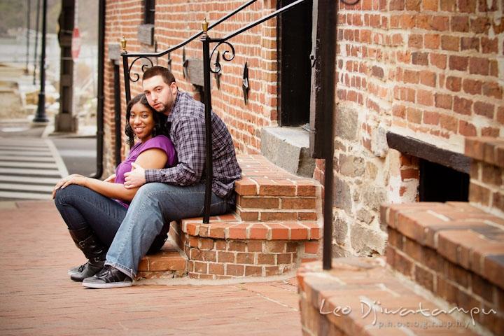 Engaged couple sitting on brick steps. Pre wedding engagement photo session at Georgetown, Washington DC by wedding photographer Leo Dj Photography