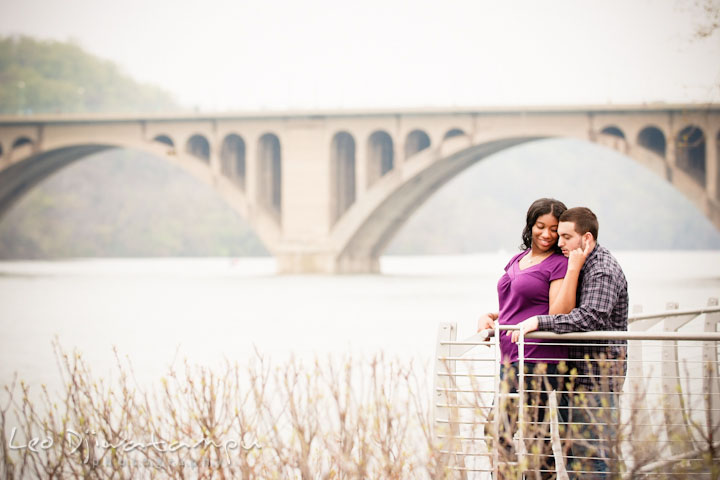 Engaged girl cuddled with her fiancé by the Francis Scott Key Bridge. Pre wedding engagement photo session at Georgetown, Washington DC by wedding photographer Leo Dj Photography