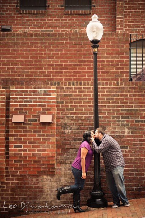 Engaged guy and girl kissing by a street light. Pre wedding engagement photo session at Georgetown, Washington DC by wedding photographer Leo Dj Photography