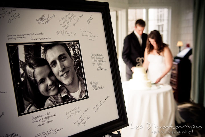 signature keepsake with engagement picture and guest signatures. bride and groom cutting wedding cake in the background. Clifton Inn Charlottesville VA Destination Wedding Photographer