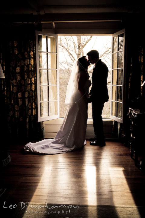bride and groom in honemoon suite, kissing by the window. silhouette. Clifton Inn Charlottesville VA Destination Wedding Photographer