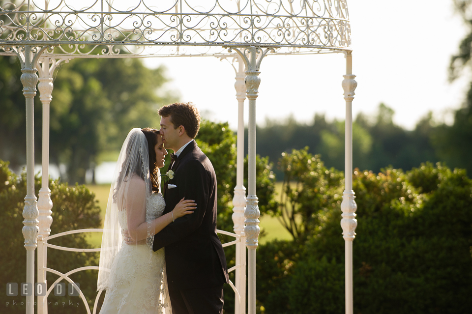 Groom kissing Bride under the pergola. Aspen Wye River Conference Centers wedding at Queenstown Maryland, by wedding photographers of Leo Dj Photography. http://leodjphoto.com