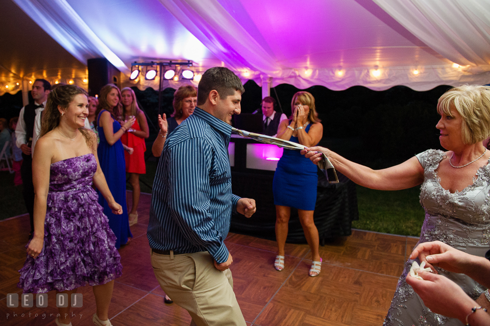 Wedding guests having fun dancing, pulling guest's tie at the wedding reception. Aspen Wye River Conference Centers wedding at Queenstown Maryland, by wedding photographers of Leo Dj Photography. http://leodjphoto.com
