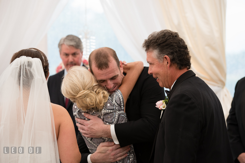 Eastern Shore Maryland Groom hugging Mother of Bride during wedding ceremony photo by Leo Dj Photography