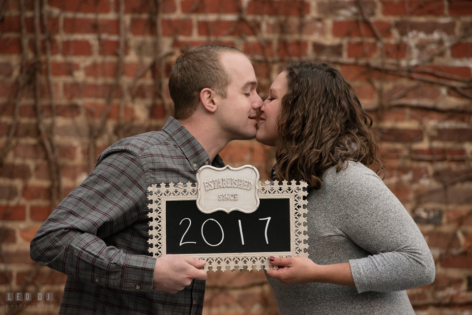 Downtown Frederick Maryland engaged couple holding wedding year sign photo by Leo Dj Photography.
