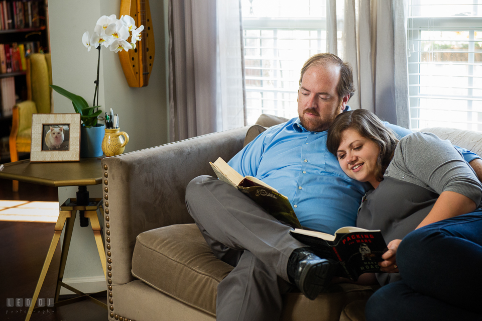 Condo Residence Baltimore Maryland engaged girl cuddling and reading together with fiance photo by Leo Dj Photography.