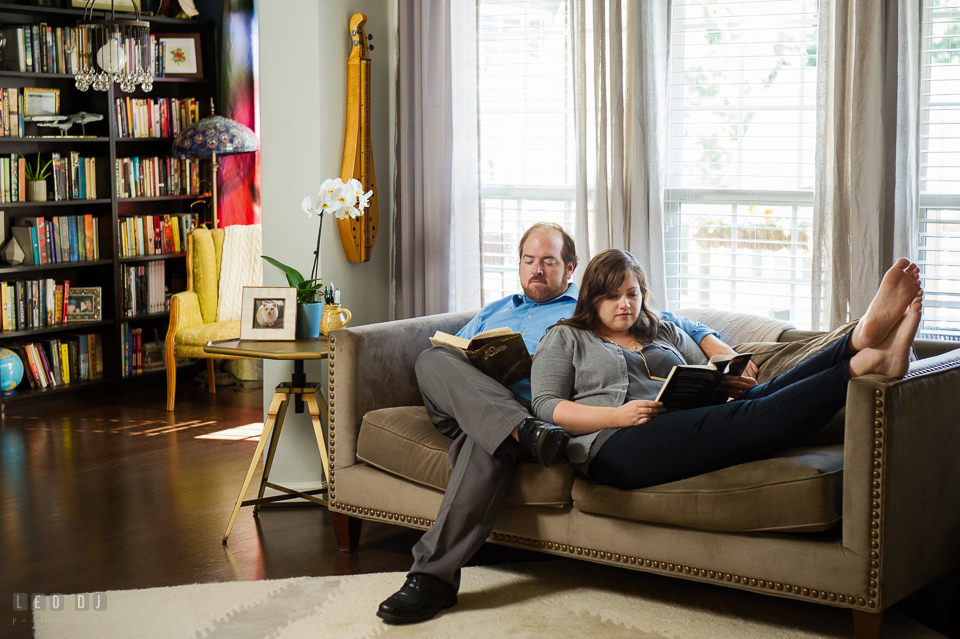 Home Residence Baltimore Maryland engaged couple lounging on sofa reading together photo by Leo Dj Photography.