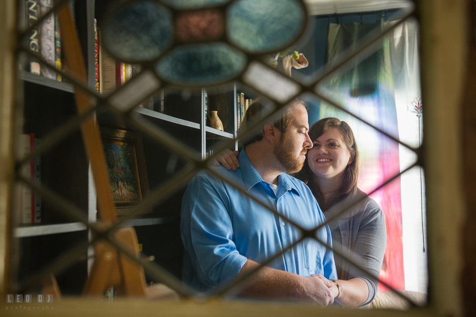 Home Residence Baltimore Maryland engaged couple hugging seen through stained window photo by Leo Dj Photography.