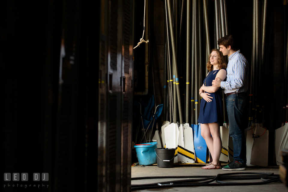Baltimore Rowing Club Maryland engaged man embracing fiancée inside boat house photo by Leo Dj Photography.