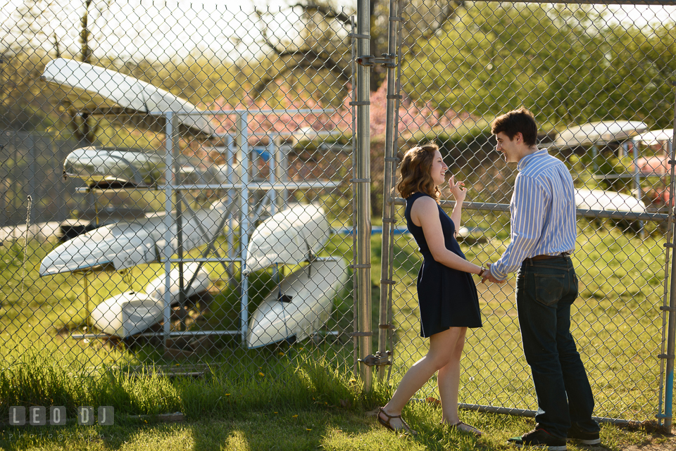 Baltimore Rowing Club Maryland engaged couple hanging by boat storage photo by Leo Dj Photography.