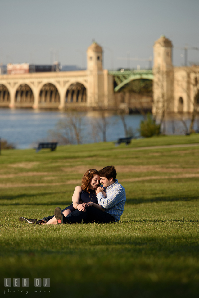 Baltimore Rowing Club Maryland engaged man cuddling with fiancée by Hanover Street Bridge photo by Leo Dj Photography.