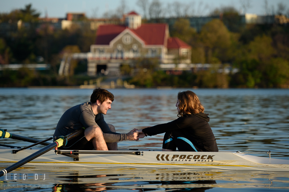 Baltimore Rowing Club Maryland engaged couple holding hands in boat photo by Leo Dj Photography.