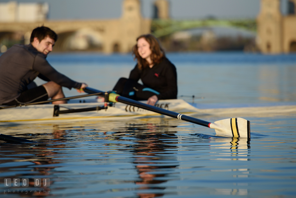 Baltimore Rowing Club Maryland engaged man rowing boat with fiancée laughing photo by Leo Dj Photography.