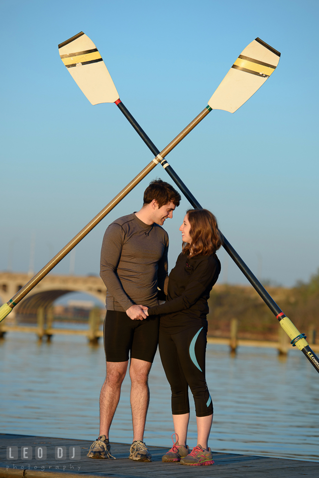 Baltimore Rowing Club Maryland engaged man holding hands with fiancee under oars photo by Leo Dj Photography.