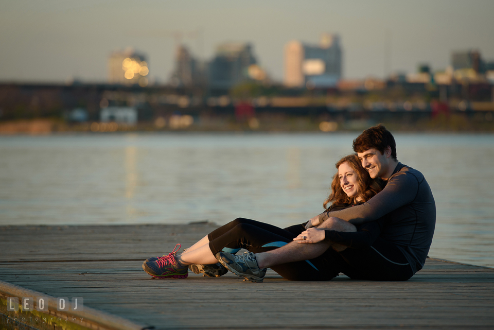 Baltimore Rowing Club Maryland engaged girl cuddling with fiancé on dock during sunset photo by Leo Dj Photography.