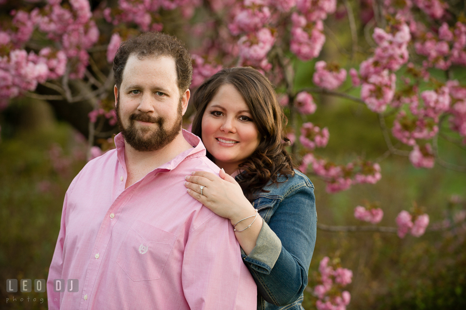 Engaged couple posing by a pink blossoming tree. Baltimore MD pre-wedding engagement photo session at Sherwood Gardens, by wedding photographers of Leo Dj Photography. http://leodjphoto.com