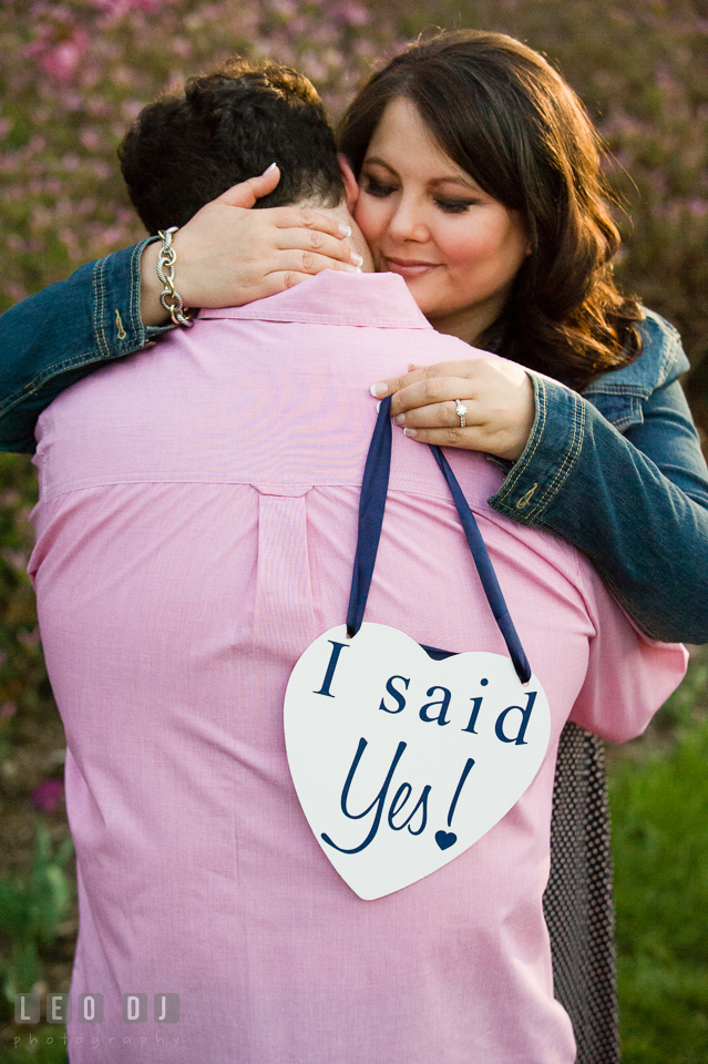 Engaged guy hugged by fiancée who is holding an I said Yes sign. Baltimore MD pre-wedding engagement photo session at Sherwood Gardens, by wedding photographers of Leo Dj Photography. http://leodjphoto.com