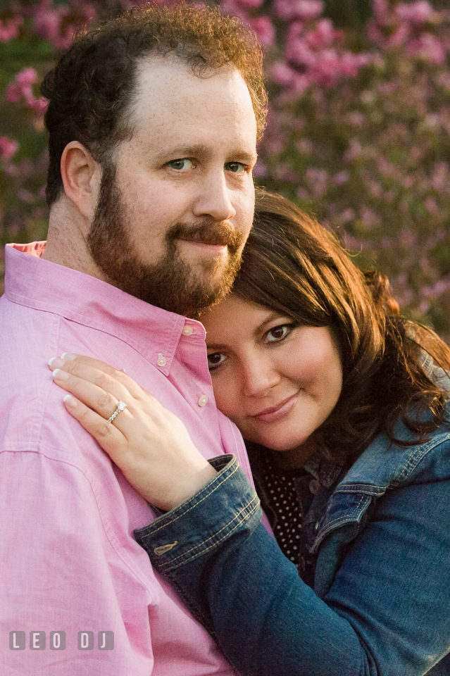 Engaged girl leaning on chest of fiancé. Baltimore MD pre-wedding engagement photo session at Sherwood Gardens, by wedding photographers of Leo Dj Photography. http://leodjphoto.com
