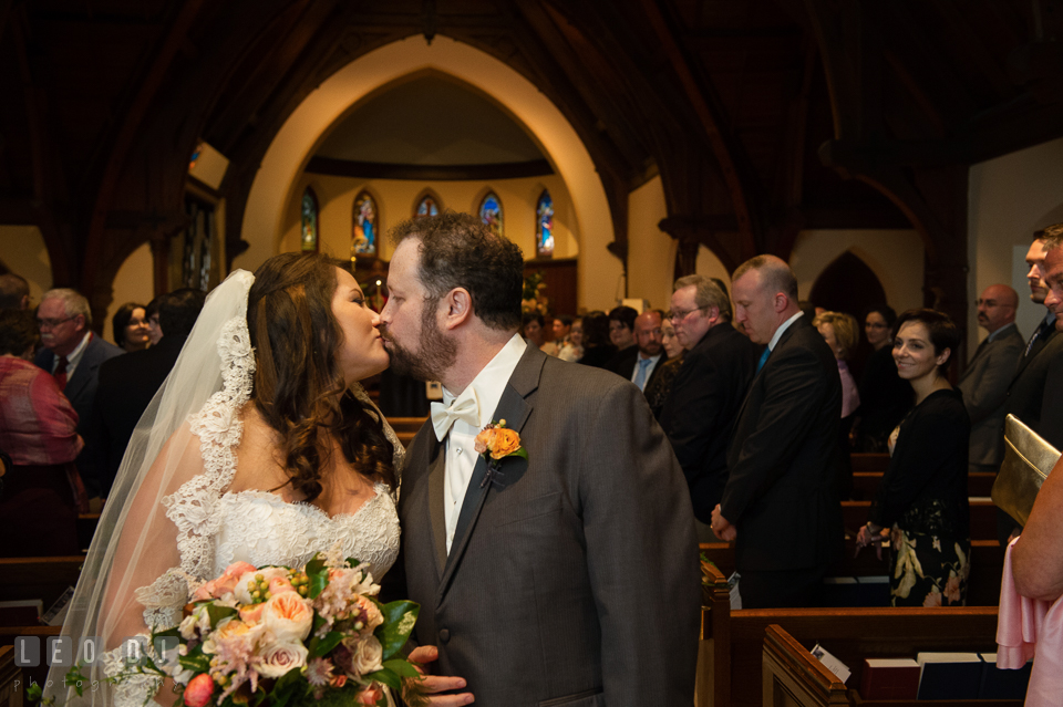 Bride and Groom kissing during the processional. The Trinity Cathedral wedding, Easton, Eastern Shore, Maryland, by wedding photographers of Leo Dj Photography. http://leodjphoto.com