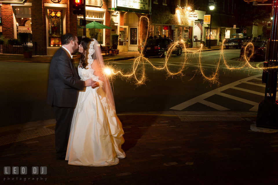Bride and Groom at downtown, kissing and holding sparklers writing love. The Tidewater Inn wedding, Easton, Eastern Shore, Maryland, by wedding photographers of Leo Dj Photography. http://leodjphoto.com