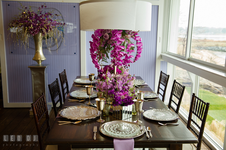 Table setting with centerpiece of purple orchids from Wicked Willow, silverware and china from Vintage Affairs. Kent Island Maryland Chesapeake Bay Beach Club Bow Ties and Bubbly wedding show photos at the Tavern Bayside, by wedding photographers of Leo Dj Photography. http://leodjphoto.com