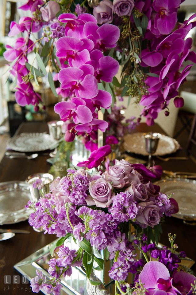 Hanging purple orchids and violet roses table centerpiece from florist Wicked Willow. Kent Island Maryland Chesapeake Bay Beach Club Bow Ties and Bubbly wedding show photos at the Tavern Bayside, by wedding photographers of Leo Dj Photography. http://leodjphoto.com
