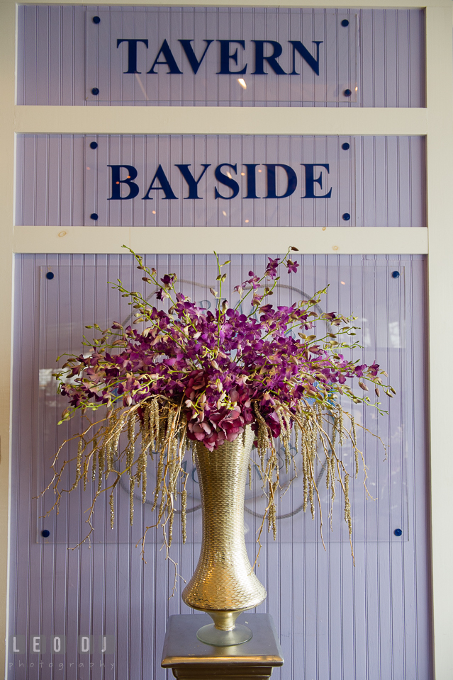 Tavern Bayside sign with vase of purple orchids from florist Wicked Willow. Kent Island Maryland Chesapeake Bay Beach Club Bow Ties and Bubbly wedding show photos at the Tavern Bayside, by wedding photographers of Leo Dj Photography. http://leodjphoto.com