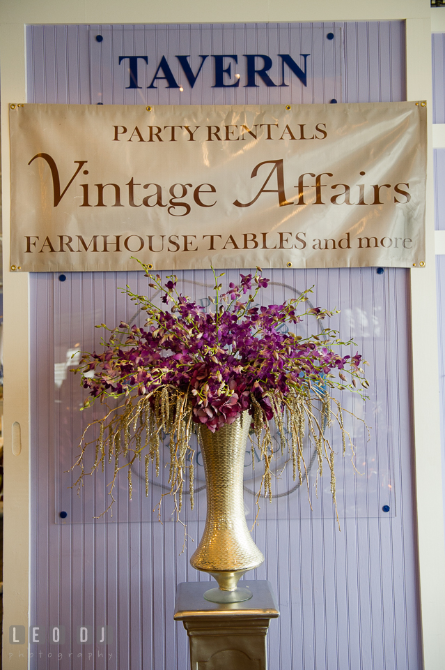 Banner sign from Vintage Affairs with a golden vase of purple flowers. Kent Island Maryland Chesapeake Bay Beach Club Bow Ties and Bubbly wedding show photos at the Tavern Bayside, by wedding photographers of Leo Dj Photography. http://leodjphoto.com