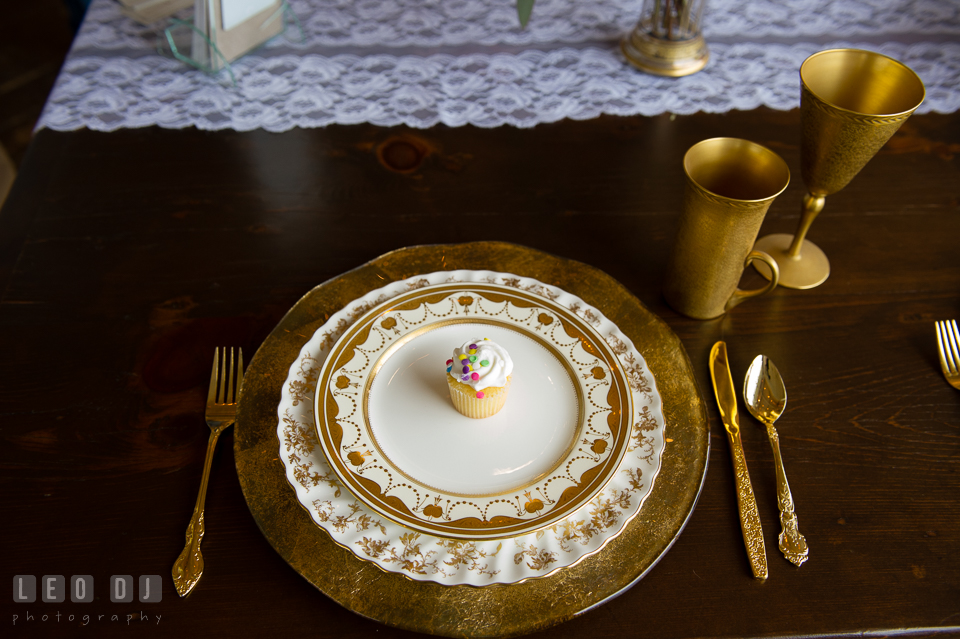 Plate setting of china, golden cups, and golden silverware from Vintage Affairs. Kent Island Maryland Chesapeake Bay Beach Club Bow Ties and Bubbly wedding show photos at the Tavern Bayside, by wedding photographers of Leo Dj Photography. http://leodjphoto.com