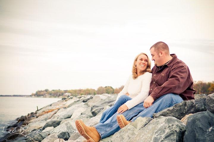 Fiancee couple smiling, sitting on rocks by water. Engagement Photographer Matapeake Beach, Chesapeake Bay