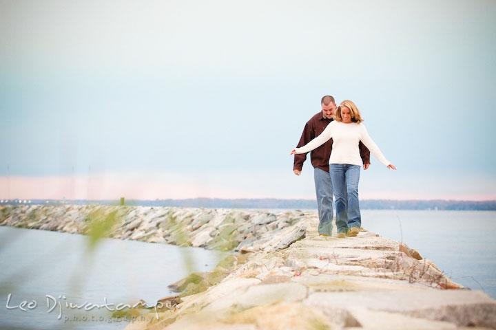 fiancee couples walking on rocks by water, Engagement Photographer Matapeake Beach, Chesapeake Bay