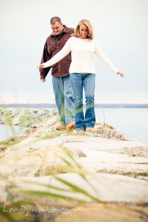 guy and girl walking on rocks by the water. Engagement Photographer Matapeake Beach, Chesapeake Bay