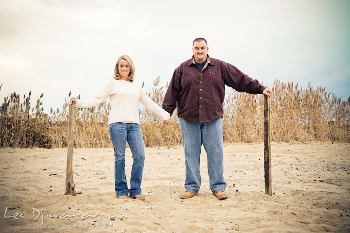 engaged couple holding hands on the beach, beach sand. Engagement Photographer Matapeake Beach, Chesapeake Bay
