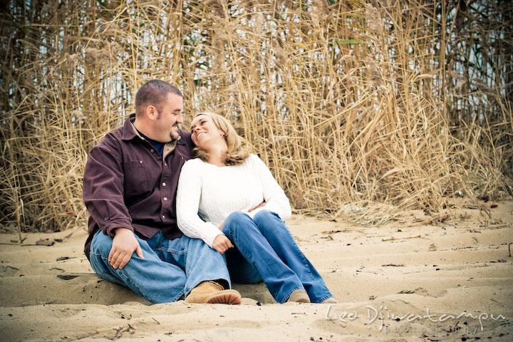 engaged couple cuddling, sitting on sand, grass straw background. Engagement Photographer Matapeake Beach, Chesapeake Bay