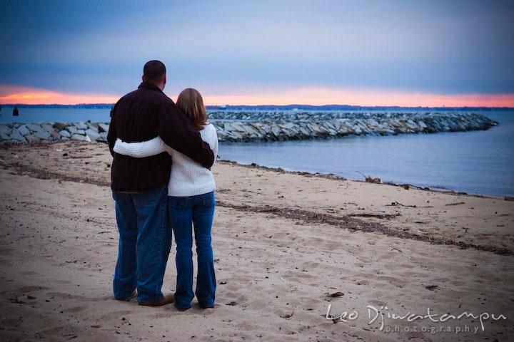 guy and girl, engaged couple, fiancee, looking at beautiful sunset color on the horizon. Engagement Photographer Matapeake Beach, Chesapeake Bay