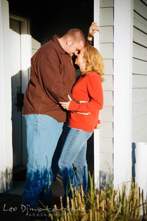 engaged couple standing by the door entryway. Engagement Photographer Matapeake Beach, Chesapeake Bay