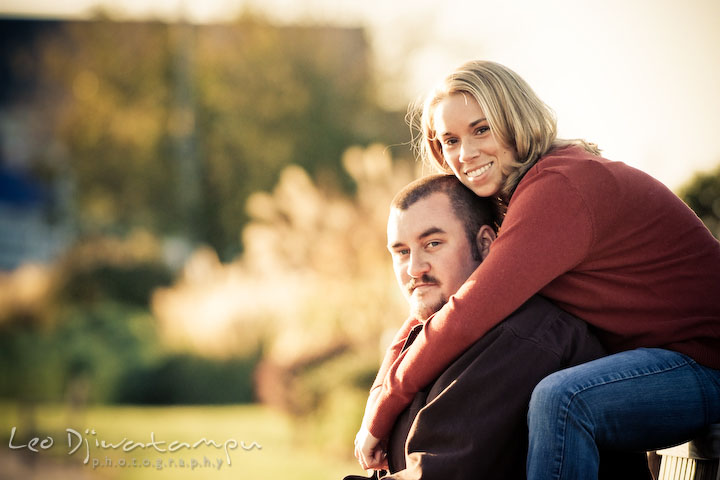 engaged girl sitting behind her fiancee guy, smiling, looking at camera. Engagement Photographer Matapeake Beach, Chesapeake Bay