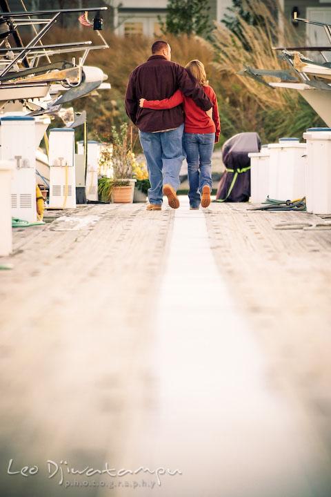 engaged couple walking on marina pier between Hemingways and the Chesapeake Bay Beach Club. Engagement Photographer Matapeake Beach, Stevensville