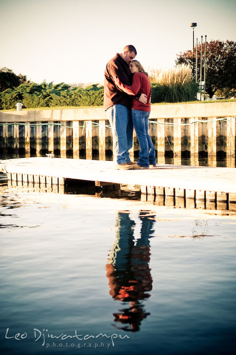 engaged couple hugging on marina pier by Hemingways and Chesapeake Bay Beach Club. Engagement Photographer Matapeake Beach, Stevensville