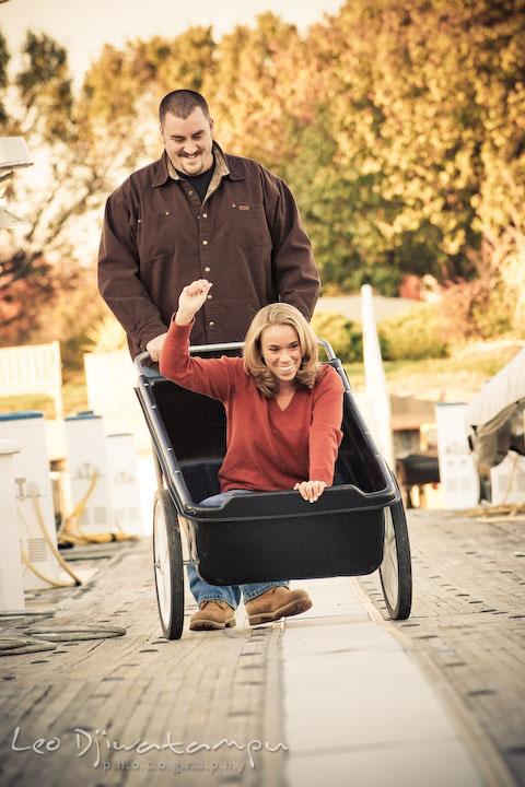 guy and girl having fun riding cart on marina pier by Hemingways and Chesapeake Bay Beach Club. Engagement Photographer Matapeake Beach, Stevensville