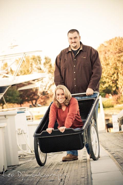 engaged couple posing. fiancee girl on cart. guy pushing cart on marina pier by Hemingways and Chesapeake Bay Beach Club. Engagement Photographer Matapeake Beach, Stevensville