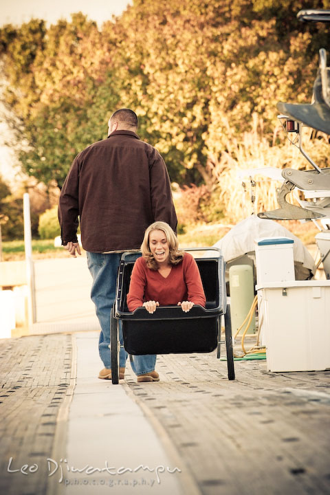 fiancee guy pulled cart with girl inside, on marina pier by Hemingways and Chesapeake Bay Beach Club. Engagement Photographer Matapeake Beach, Stevensville