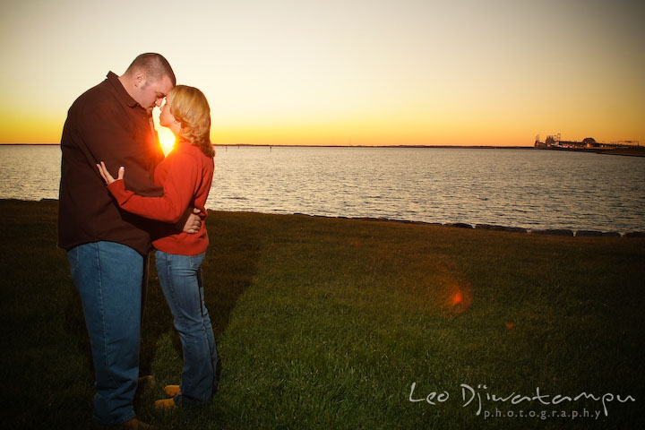 engaged guy and girl hugging with golden suset behind them, overlooking at the bay bridge and annapolis. Engagement Photographer Matapeake Beach, Stevensville