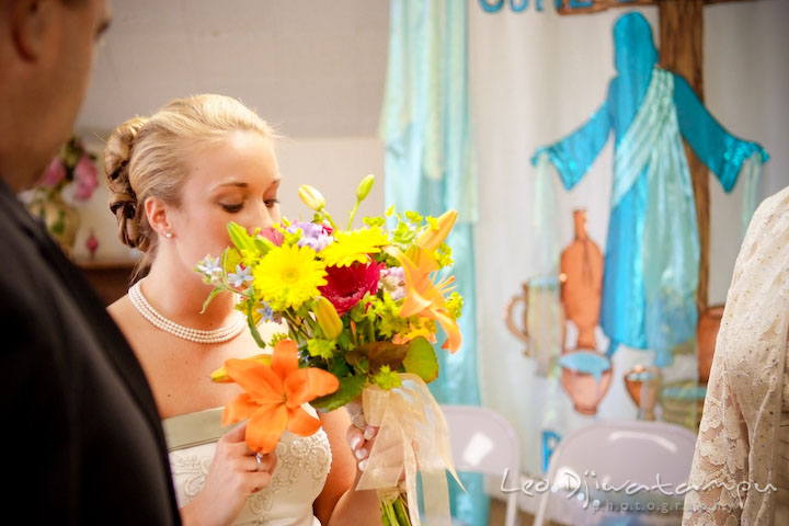 Bride smelling the flower bouquet's nice aroma. Kent Island Methodist Church KIUMC Wedding Photographer Maryland
